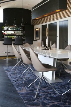 Rug, dining chair and dining table come together to make the living room compliment the bar area
