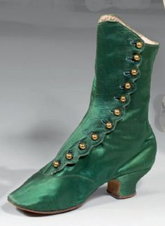 Paire de bottines à talon pour femme, milieu XIXème siècle. Satin vert émeraude, fermeture sur le côté par 5 petits boutons ronds dorés nécessitant l'usage du crochet à bottine dit tire-boutons. Ce dernier, devient un élément indispensable de toute garde-robe féminine dans les années 1880 ; quant au retour du talon, amorcé sous Louis-Philippe, il devient habituel et prend la forme d'une demi-bobine. Edwardian Shoes, Victorian Shoes, Victorian Women, Victorian Fashion, Vintage Fashion, Victorian Era, 1930s Shoes, Antique Clothing, Historical Clothing