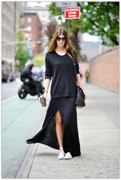 Love the split black maxi dress worn with larger v neck black jumper over the top & white runners.
