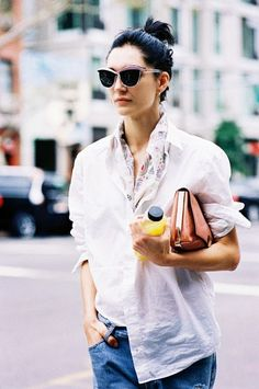 A silk scarf is worn lined at the collar of a simple white button-up and paired with blue jeans for a casual look.