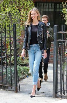 Karlie Kloss wears a black top, leather biker jacket, cuffed jeans, and black pumps