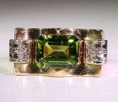 """Vintage Retro Peridot and Diamond Ring, 18k Gold from vsterling on Ruby Lane    """"Peridot is the only gemstone found in meteorites. Granted this particularly lovely bright olive green emerald-cut Peridot is most likely Earth-made, but I find it fascinating to think of all those big chunks of rock flying through the cosmos with these lovely green crystals along for the ride. Is is just coincidence that Kryptonite looks a little like Peridot? I think not…"""""""