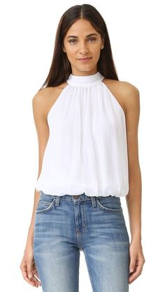 Elastic gathers the balloon hem of this alice + olivia blouse. The halter straps tie in a playful bow, and draped panels form a cutout in back.