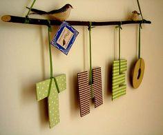 Letras revestidas com tecido e amarradas por fitas num galho seco. As letras podem ser feitas em MDF, Papel Holler ou mesmo Papel Pluma, que você mesmo recorta usando um estilete de precisão.