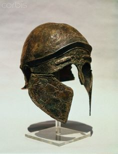 Etruscan helmet. The cheek guard is decorated with a scene of two fighting men carrying round shields.  Located in: Italy.