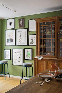 """Wenn Jasmin Khezri in der Küche sitzt, blickt sie auf Farrow & Balls """"Yeabridge Green"""" und ihre eigenen Werke: """"Das fühlt sich für mich behaglich an."""" Die Ikea-Barhocker wurden mit Kissen von Pierre Frey veredelt. Der Schrank stammt von einem Londoner Flohmarkt, das Geschirr ist von Royal Copenhagen. (Foto: Elias Hassos)"""