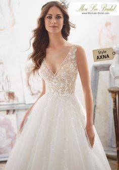 Style AXNA Matilda Wedding Dress  Crystal Beaded Floral Embroidery Accent the Illusion Bodice and V Back on This Classic Tulle Ballgown Creating a Soft, Romantic Look. Colors Available: White, Ivory, Nude/Ivory. Shown in Nude/Ivory.