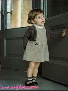 La petite fille porte une robe grise avec un manteau brun et chaussures noir