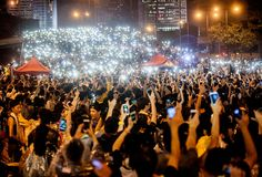 Tens of thousands of Hong Kong protestors, protecting themselves from tear gas   with masks and umbrellas, calmly demonstrate for greater democracy in China