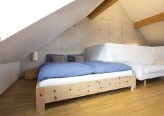Modernes metallfreies Zirbenbett ohne Kopfhaupt im Dachloft. Das Zirbenholz wirkt sehr harmonisch zu der Mauer aus Sichtbeton.