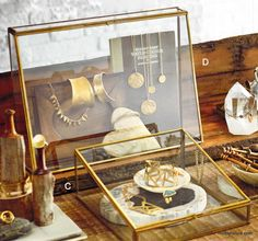 Versatile angled brass- edged cases are the perfect showplace for jewelry or other precious items. Glass panels are framed in brass- plated iron on each case; a hinged door has a slide latch. Two sixes of cases may be oriented vertically, for use with jewelry stands, or horizontzlly for myriad items.