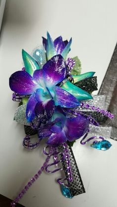 Blue bomb orchids with purple and black accents wrist corsage