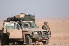 A U.S. fighter stands near a military vehicle, north of Raqqa city, Syria November 6, 2016.  Toyota 76 series land cruiser