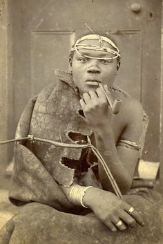 South Nguni (Xhosa) man, possibly a shepherd, wearing a sheepskin kaross and smoking a typical Xhosa pipe. Very early pic probably