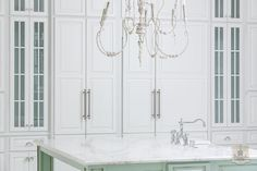 A+whitewashed+French+candle+chandelier+hangs+over+a+mint+green+kitchen+island+with+turned+legs+topped+with+white+marble+with+gray+veining+fitted+with+a+farmhouse+sink+and+deck+mount+faucet.