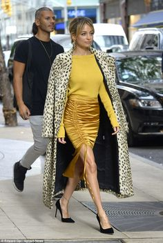 A walk on the wild side: The reality star turned fashion designer, 36, looked stylish in an eye-catching silk mustard pencil skirt with a dramatic thigh-split and ruched detailing