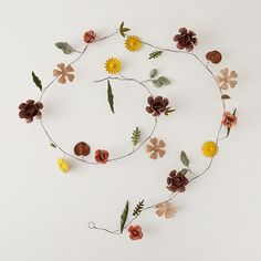 """Metal blooms in an assortment of shapes and hues adorn this delicate strand for sprucing up natural décor.- Metal, wire- Wipe clean with damp cloth- Indoor or sheltered outdoor use- Imported3""""W, 69""""L"""