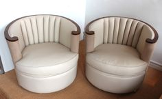 An immaculate pair of Art Deco tub chairs of stunning proportions by Maurice ADAMS. Veneered walnut scrolled arms. Upholstered in ivory leather and contrasting oatmeal Alcantara suede. English, c.1930. (hva)