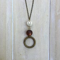 Long copper colored necklace with beaded pendant.