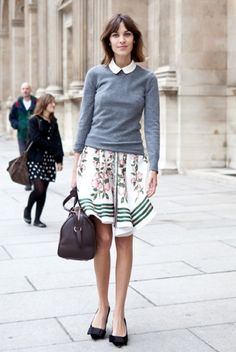 Alexa Chung. Full skirt with a print, neutral sweater, white collared shirt under, adorable flats