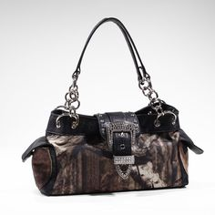 Emperia Women's Naomi Mossy Oak Buckle Tote Bag with Rhinestones, Camouflage/Black Trim, 13.5 x 4.5 x 8-Inch. Licensed Mossy Oak product. Top zipper enclosure. Two side flap pockets with magnetic snap closure. Flap with bling buckle decorated and with magnetic snap.
