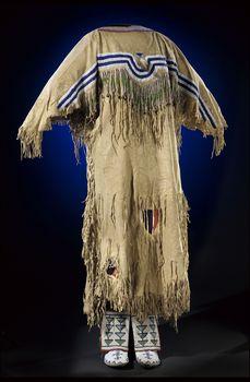 Culture/People:Niitsitapii (Blackfoot/Blackfeet) Object name:Woman's dress Date created:circa 1890 Place:Gleichen; Alberta; Canada Media/Materials:Hide, glass bead/beads, wool cloth, brass bell/bells, sinew Techniques:Sewn, lazy/lane stitch beadwork, fringed