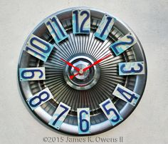 License Plate and Hubcap Clock. Numbers made with Washington state license plate numbers. Hubcap is an old Pontiac hubcap. Made by Jim Owens