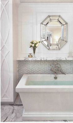 I'd be striking my knees against that tub every morning, but the mirror is lovely. Like that wall treatment to the side, too.