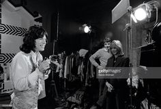 Rolling Stones' Mick Jagger takes a photograph on the set of 'Performance' with Anita Pallenberg in the background, Shepperton Studios, London, September 1968.