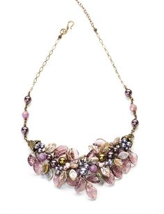 Purple beaded necklace with a lovely cluster of leaves and Swarovski pearls. The pearls and beads lay in a bed of glass leaves making for a