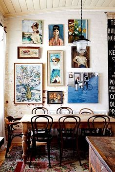 Gallery wall of modern and vintage paintings in a rustic dining room - Eclectic Gallery Art Wall Ideas & Decor