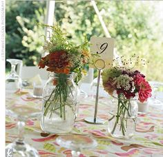 Mason jars filled with brightly colored wildflowers from a local farm adorned each table along with white linens and round, patterned cutout...
