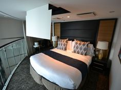 Royal Caribbean  QUANTUM OF THE SEAS: Grand Loft Suite with Balcony. The master bedroom of the Grand Loft Suite has a king size bed that can be converted into two twin beds. The bedrooms overlook the main floor of the room below.