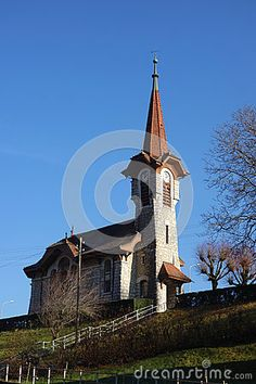 Photo about An old narrow church with a clock tower steeple atop a hill in Switzerland. Image of castle, clock, small - 89803974 Statue Of Liberty, Switzerland, Castle, Tower, Stock Photos, Mansions, House Styles, Building, Clock