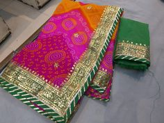 Bandhini 60 gm Georgette saree with gota work on the borders. Comes with contrast color blouse with gota borders. Pure Georgette Sarees, Silk Sarees, Indian Sarees, Bandhini Saree, Gota Patti Saree, Bollywood Outfits, Bollywood Style, Bridal Mehndi Dresses, Stylish Dress Designs