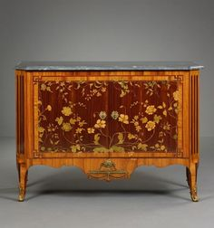 A DUTCH TRANSITION COMMODE WITH MARQUETRY, ca. 1775. Material: oak frame veneered with amaranth, boxwood, rosewood and bois teinté, gilded bronze fittings, Bleu Turquin marble top. H. 91 cm / 36 in, W. 60 cm / 24 in, L. 123 cm / 48 in