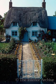 A white garden gate opens on to a narrow path leading up to the entrance of this thatched cottage