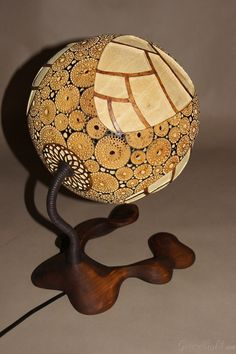 https://flic.kr/p/jDkHLA | Table lamp IX | Head of the lamp is made of Senegalese calabash. White parts are carved layer of the fruit which change the color to red/orange when the lamp is switched on. On the bottom of the lamp there's perforated closing part locked by magnets. The lamp was painted with wood oil and alcohol ink. Black parts are burnt calabash surface. The center element is genuine Baltic amber- ranked as the world's finest;  resin from the ancient trees dating back ~40…