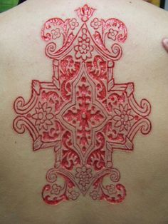 scarification: cutting designs into skin with a scalpel. when the cuts heal scar tissue forms into the design that was carved