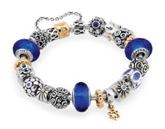 This bracelet displays royal blue Italian Murano glass charms, pops of bright 14k gold that contrast beautifully with the crisp sterling silver