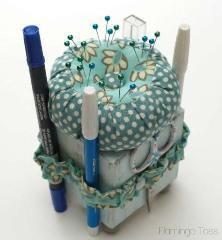 Bev from Flamingo Toes shares a tutorial showing how to make a sewing tool caddy and pincushion. The base is a 3×3 wood block,wrapped with a fabricstrip to hold tools and topped with a matc…