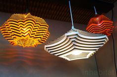 """<h2><a href=""""http://www.artisandsi.com/pendant-lighting"""">Cardboard Lamps by Artisan Design Source</a></h2>  <a href=""""http://www.artisandsi.com/"""">Artisan Design Source</a> gives cast-off cardboard a new life by transforming it into stunning pendant lamps. Each lamp is made from sheets of recycled cardboard and acrylic that are laser-cut and stacked to form striking shades."""