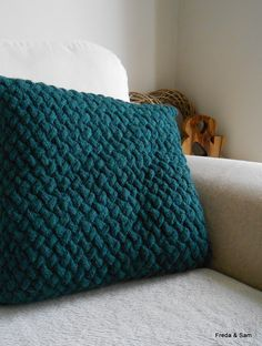 Hand knitted cushion in dark green chunky yarn. The basketweave pattern is on the front and only and the back is plain knit. The opening is in the centre of the back and held together by five plain green buttons.