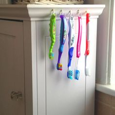 Pinterest Inspired.......Martin Perfected!! No more dirty moldy tooth brush holders, or wondering what to do with that fifth toothbrush and only four holes!! Hooks from the hardware store, and Handy Hubbys wonderful drilling technique to add holes in our toothbrushes and WALLA!! The best, most wonderful, organized tooth brush holder EVER!!