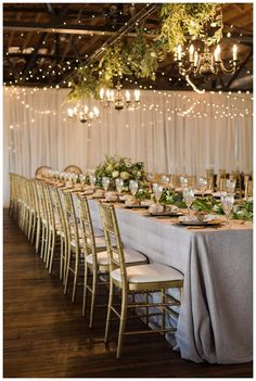 Wedding reception at Summerour Studio in Atlanta, designed in a palette of gray and gold with floral chandeliers, floral garland and sheer drapery. Event design by Molly McKinley, florals by Victory Blooms. Image by Rustic White Photography.