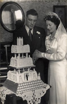 "1940s. ~ I love the square tiers of this wedding cake! Who says square cakes are anything ""new""? And one of the very few old photos where you can get even a glimpse of the bride's new wedding band. I love old wedding band photos too!"