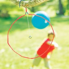 Air Golf Game - Setup: Shape the wire hangers into circular targets as shown. To make the targets easier to see, wrap the wire with crepe paper or colored tape. Suspend a jingle bell from a string in the center. Hang the targets in trees or from play structures. Players take turns throwing their ball or disk through the open space in the hanger. Scoring is similar to golf.