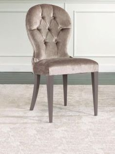 The Luxurious velvet button backed dining chair is hand carved from solid beech wood with a special spring grey polished finish. Shown here with the with seat and back upholstered in a fawn velvet fabric with silver stud detail.