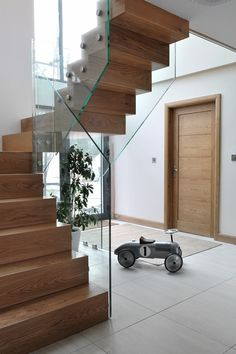 A modern glass staircase with clean lines to complement the open plan living space. Modern Hallway, Modern Entrance, House Entrance, Entrance Hall, Cottage Stairs, Cottage Front Doors, New Staircase, Modern Staircase, Glass Door Coverings