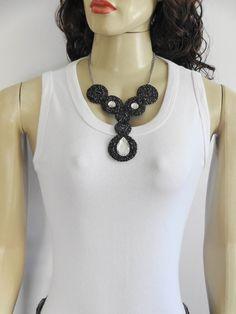 Maxi colar de crochê, elaborado em fios de polipropileno nas cores preto e metálico, com aplicações de cristais de acrílico, corrente niquelada e fecho boia. R$ 27,00